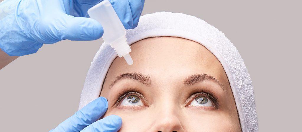 Kowa Mädchen mit Augentropfen. Arzt Hände Anwendung Augenwäsche. Rückgewinnung KataraktVerfahren. Konjunktivitis-Behandlung. Gesundheits-Ophthalmologisches Konzept. Augenklinik. Antiallergisches Medikament.